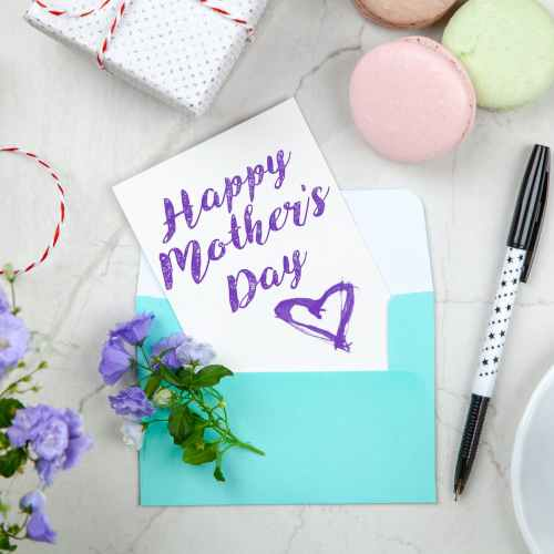 happy mothers day card beside pen macaroons flowers and box near coffee cup with saucer