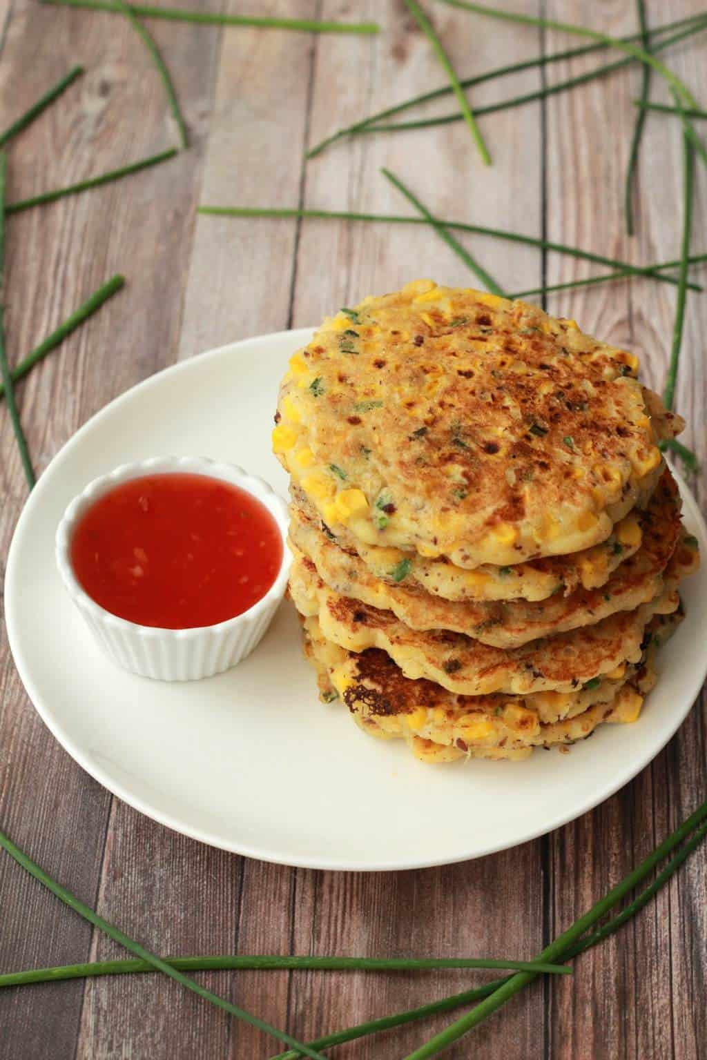 Vegan corn fritters stacked up on a white plate.