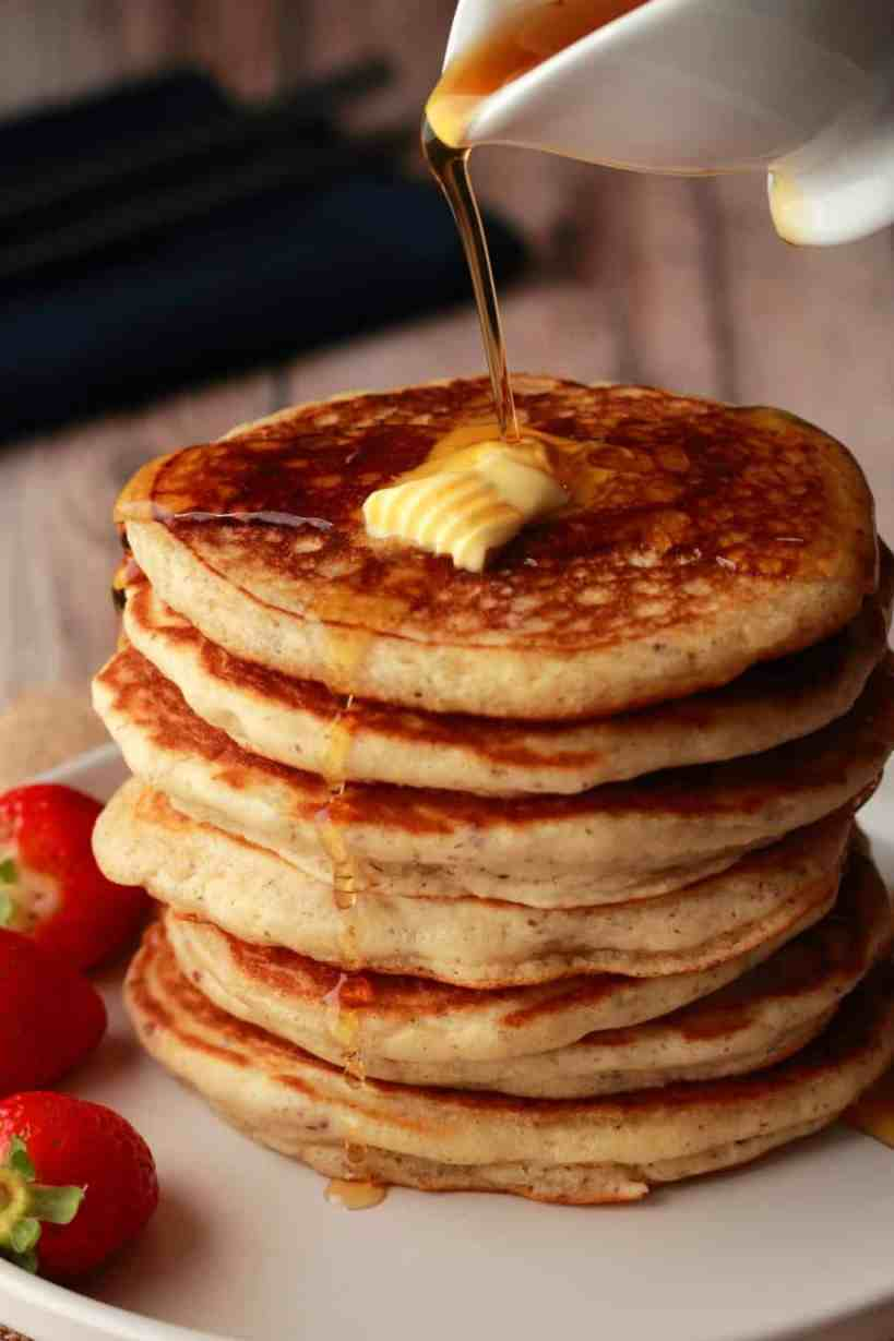 Syrup pouring over a stack of vegan pancakes.