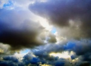 dark-cloud-in-blues-and-grays-with-the-sun-behind_2443793-300x218