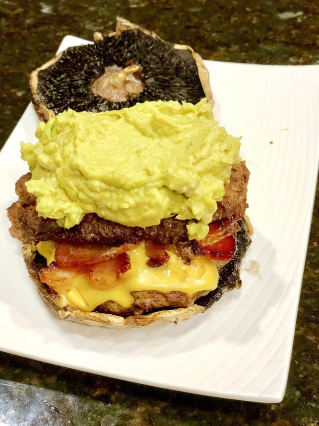 Cajun double cheeseburger with bacon, chipotle aioli avocado mash, on top of a portabello bun