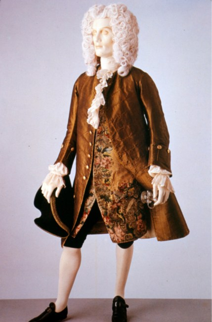 """""""This coat and waistcoat illustrate formal daywear for men in the 1740s. The fabric of the coat is a rich shot green and black silk. By the 1740s the waistcoat is shorter in length than the coat. It is made of yellow silk brocaded with coloured silk and silver threads. Comprised of large flowers and leaves densely covering the fabric, the brocaded pattern is typical of Late Baroque design. The coat is collarless. It fits tightly to the body, but has very full skirts pleated to the sides at the hip. The sleeve cuffs are wide, reaching about half way to the elbow. Typical of the early 18th century, the waistcoat is also sleeved, although this style was beginning to go out of fashion by the 1740s."""" Victoria & Albert Museum, 1745"""