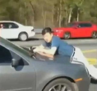 man calmly rides on hood of car