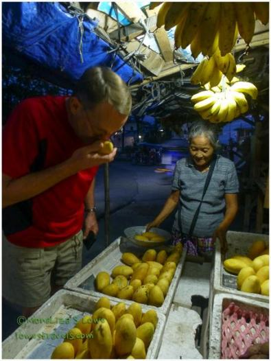 """""""Sniffing"""" mangoes at a produce stand"""