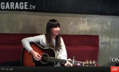 Natsuko Miyamoto clutching a guitar on a live webstream