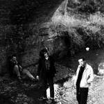 Rob, Jim and a long haired Ben stood and sat under an arched bridge across a river