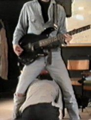 Jim crawls through the legs of Ben who is playing bass, for reasons unknown