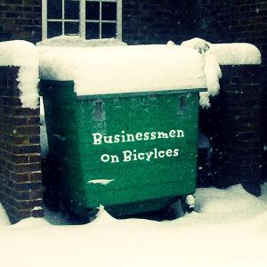 A large commerical rubbish bin with the words Businessmen On Bicycles on the side which links to the page of the aforesaid band