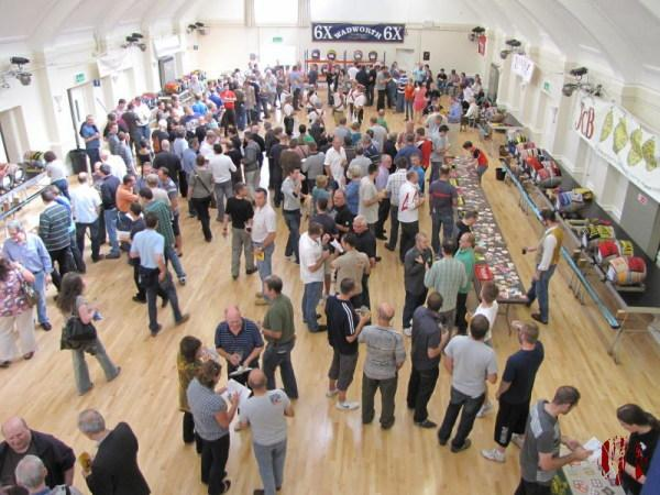 """The Main Hall of the Drill Hall with barrels arranged around the sides on staging at one metre height and racking at the far end. In the middle are about 300 drinkers and to the side the Broadwood Morrismen band who can be heard in the clip."""" /></p> <p>The recording is from 11th September but the photograph the 12th."""