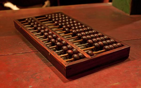 A photograph of a Chinese abacus on a wooden work surface, perhaps a ... counter.