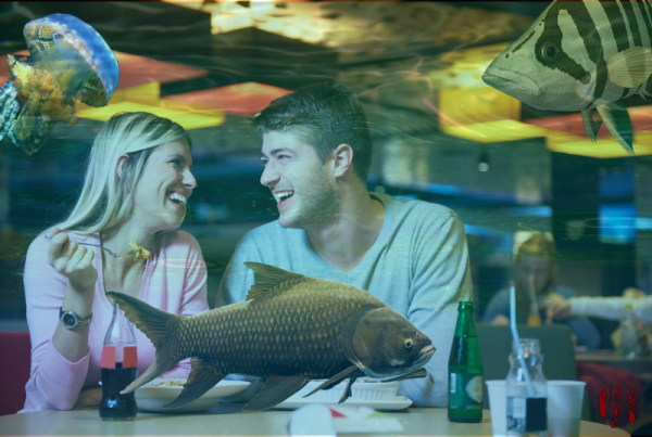 Youngish couple look at each other whilst eating in a restaurant whilst badly superimposed fish swim by.