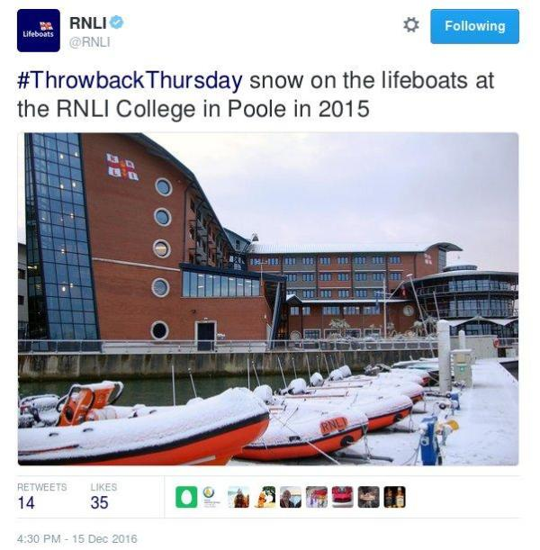 A Tweet by the Royal National Lifeboat Institution showing several rigid inflatable bright orange life boats with a thin layer of snow on them drawn up on shore outside their training college.