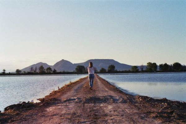A woman walks away from the camera on a narrow muddy bank between would looks like two resevoir lakes.