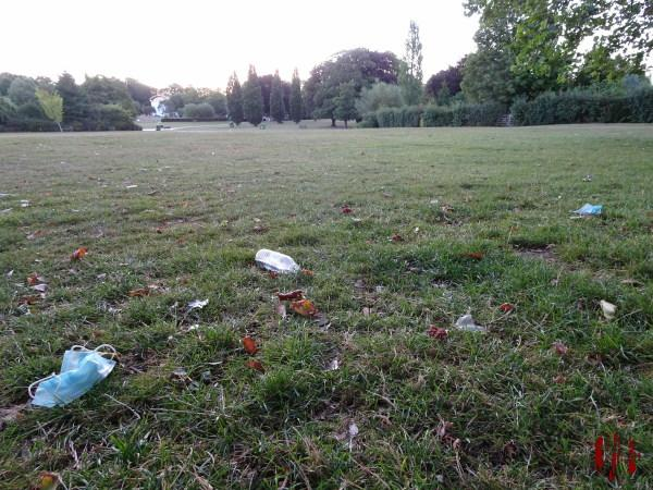 A view of Horsham Park seen over a discarded face mask and other rubbish in the time of Coronavirus Covid-19.