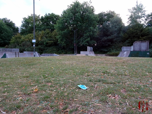 A view of Horsham Park towards the skate park seen over a discarded face mask in the time of Coronavirus Covid-19.