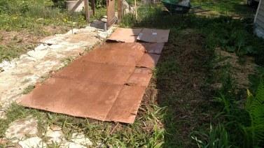 Cardboard sheet mulch before being buried in straw.
