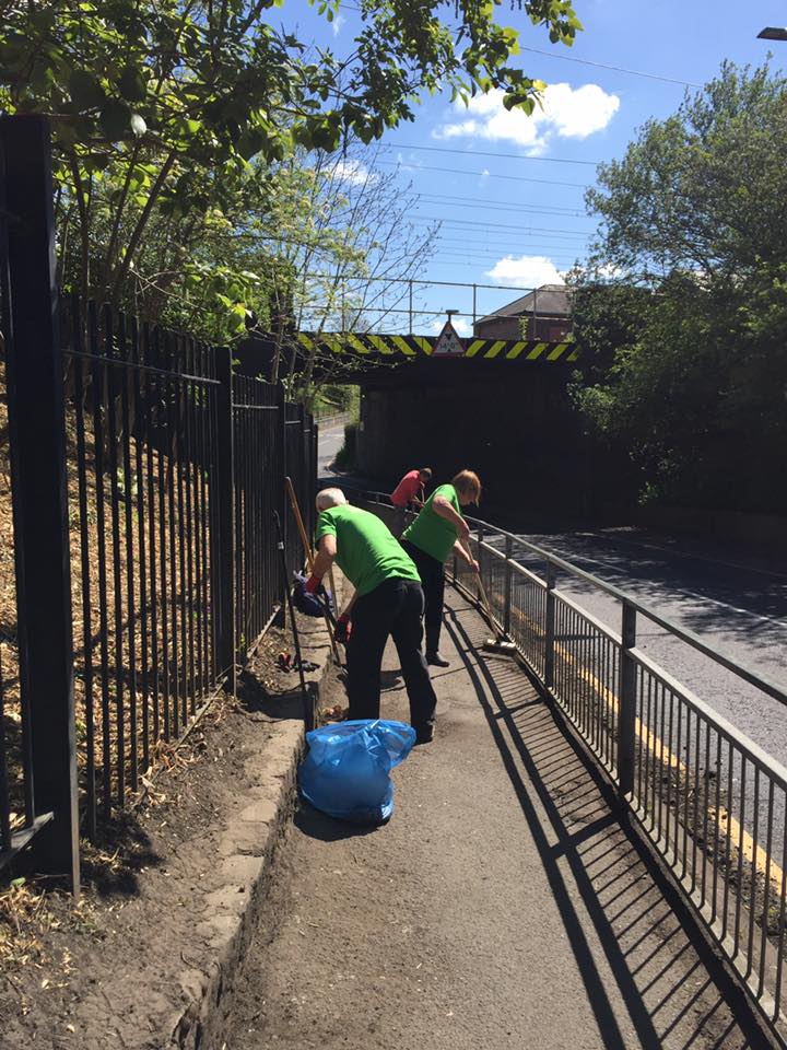 Golborne in Bloom tidying the pavement alongside Tanners Lane