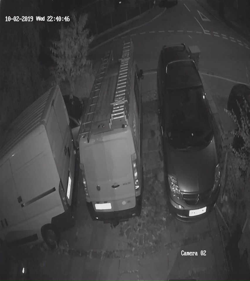 A CCTV still showing vans parked on a driveway at night