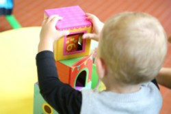 Baby plays with blocks in childcare setting such as a nursery