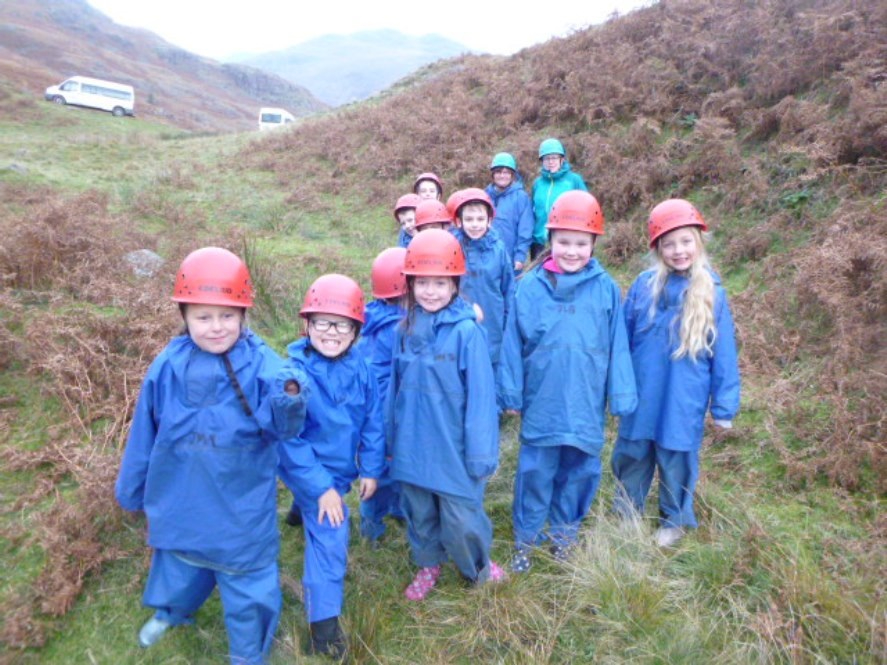 A group of primary school pupils in waterproof clothes and hard hats standing on a hillside