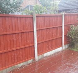A garden fence stained red by Liberty Outdoor Maintenance Ltd in Golborne