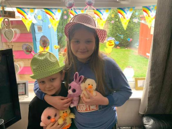 Two children with Easter bonnets and decorations