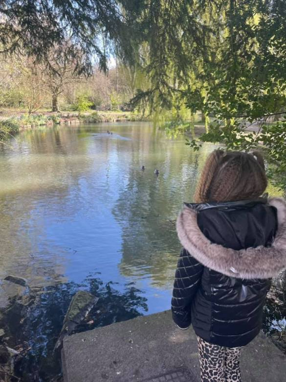 Girl looks out over a pond