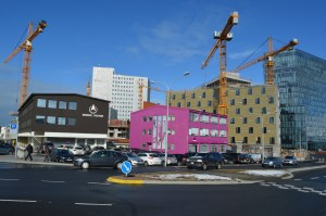 Pink WOW Air Building in downtown Reykjavik surrounded by construction cranes.