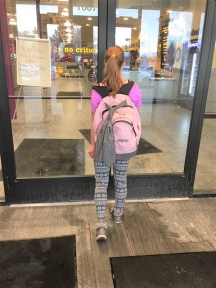 LoyalYak ShoeSling hanging on backpack with young woman walking into fitness center