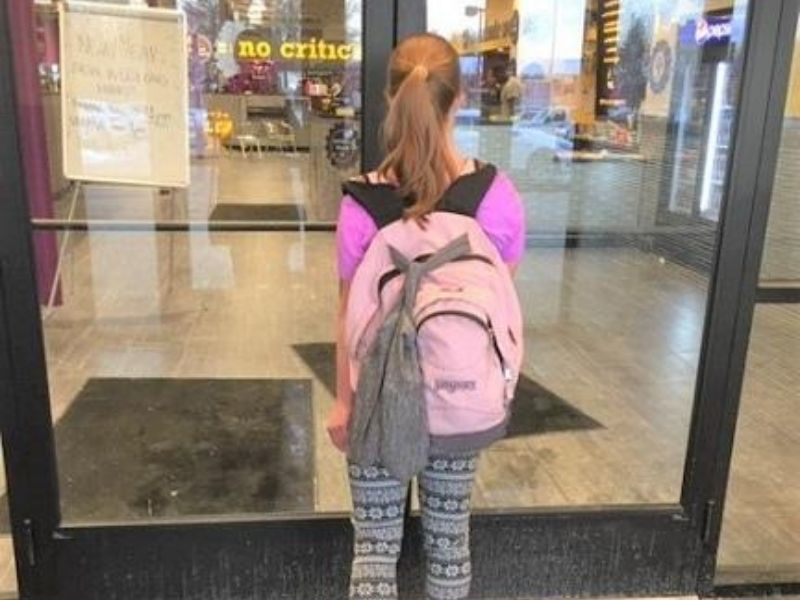 Child walking into a gym with the ShoeSling on her backpack