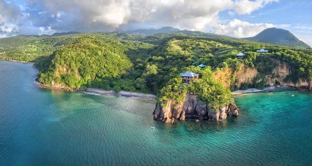 Veduta aerea del Secret Bay Hotel, costruito su una grande scogliera e circondato da grandi alberi;  resort eco lusso