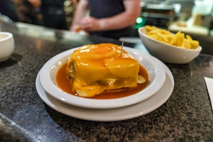 A francesinha in on a white plate, which sits on top of a bar. It's smothered with sauce and behind it sits a bowl of fries. A member of staff is out of focus, behind the bar.