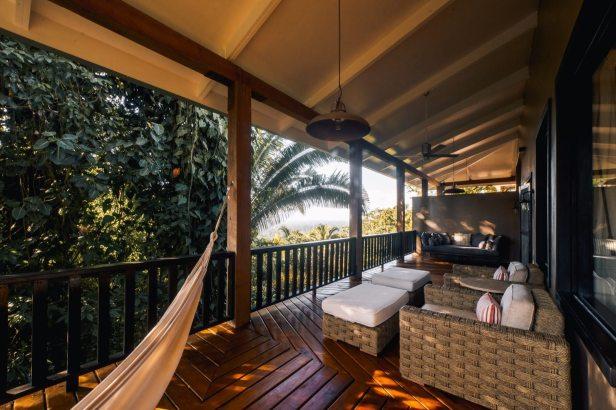 Un'amaca è legata al lato di una terrazza, mentre una coppia di sedie e un divano riempiono il resto dello spazio sulla terrazza in legno;  resort eco lusso
