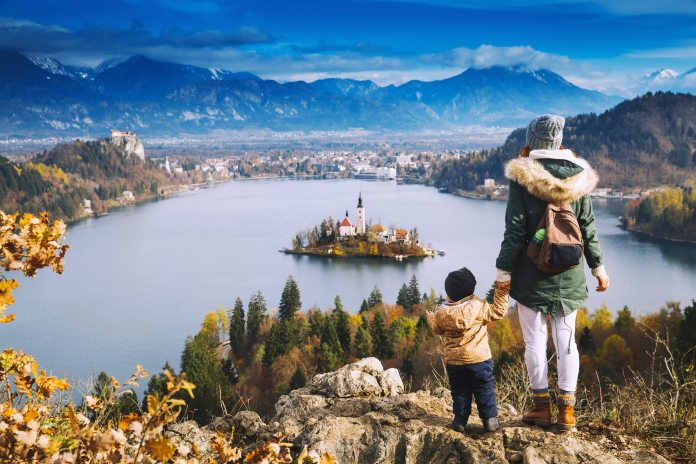 An adult and child look down over Lake Bled in Slovenia from a hilltop