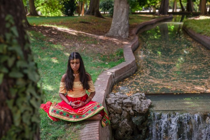 A young Indian woman does yoga outside