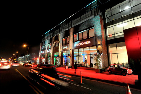 Photo of exterior of three story building at night with brightly lit windows and bright red carpeted walkway