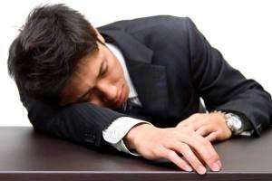 疲れて机に突っ伏す男性