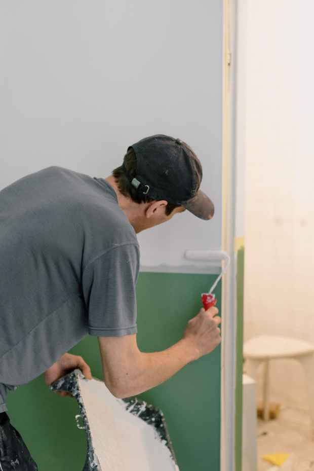 man painting walls in new home. builder