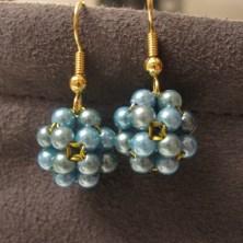Fine blå perlekugler på ørekroge
