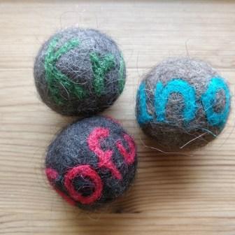Filtede bolde af pels fra hunde og katte, med nålefiltet navn på.