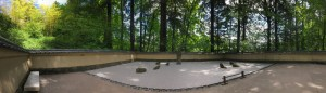 Panorama view of the Portland Japanese Garden, showing a low stone wall and lots of tall trees around the perimiter