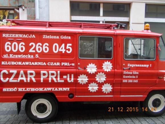Czerwony samochód reklamujący restaurację Czar PRL-u.