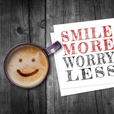Image of a coffee with smiley face designed on the foamed latte, with a sign that reads smile more worry less. This reinforces the notion of flipping the script and focusing on the positive and what we are in control of.