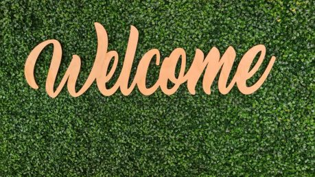 Welcome in orange written on a patch of grass, welcoming you to The Lost Labia Chronicles.