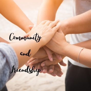 Image of a group of people putting their hands together representing community and friendship.