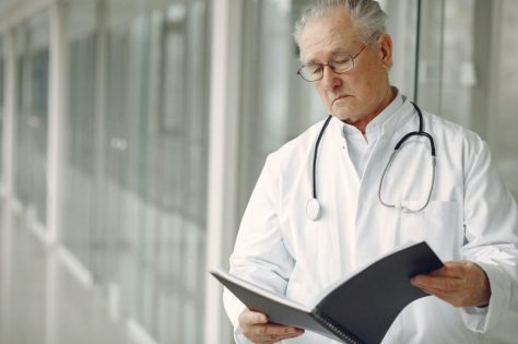 Image of a stern looking doctor, looking annoyed while reviewing a case file. This image represents the number of doctors in the medical symptom treating Heather as though her symptoms were her fault or nothing to be concerned about.