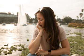 Image of a person outdoors, looking disappointed. This represents the disappointment and anger I felt towards my body.