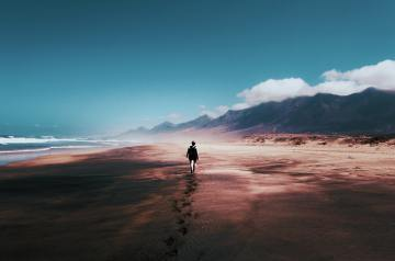 Image of a person walking on a beach, their footprints behind them and a journey in front of them. This image represents the ongoing journey of acceptance and resilience.