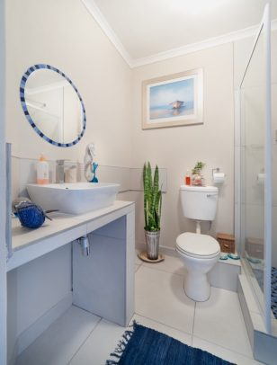 Image of a bathroom with a sink, shower, and toilet. This represents how I first learned to relax and do reverse Kegels on the toilet.