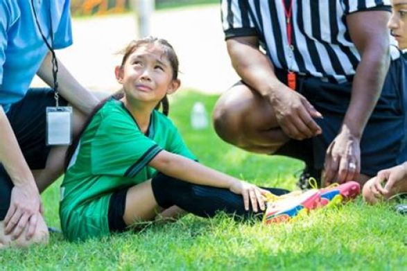 Child injured playing sport receiving first aid.